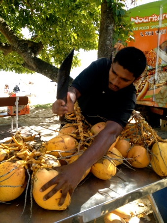 A street vendor selling fresh coconuts in Grand Baie.