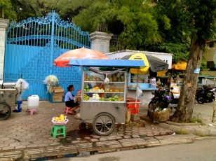 A woman having breakfast on her way to work at one of the street-side stalls in Phnom Penh.