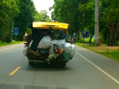 There are three men, a scooter and a couple of large sacks hanging out the back of this van. We got this shot through our windscreen as we followed at highway speeds.