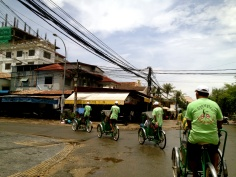 Two iconic images of Phnom Penh - the cyclos and the power lines.
