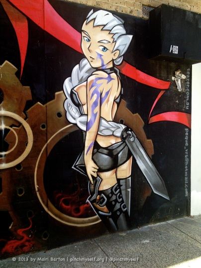 A gun and sword-wielding female super hero lurking in the laneway just in case she's needed by the nearby cafes and shops.