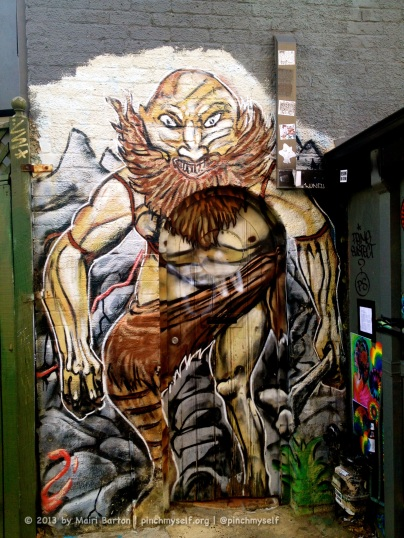 This cave man lurks in a little alcove behind another building. I love the way the artist has been able to continue the work right across the doorway so effectively.